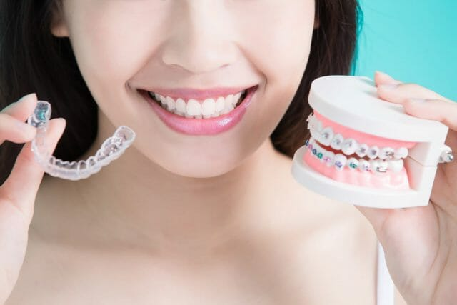 Woman holding up invisible aligners and model of braces